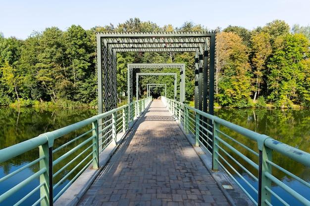 Ponte pedonal sobre o rio no rio com árvores e reflexo na água.