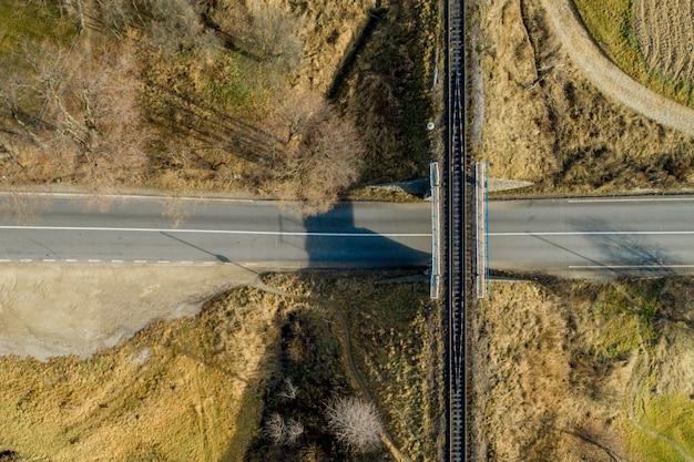 Ponte railway entre prados verdes sobre a estrada na zona rural, vista aérea.