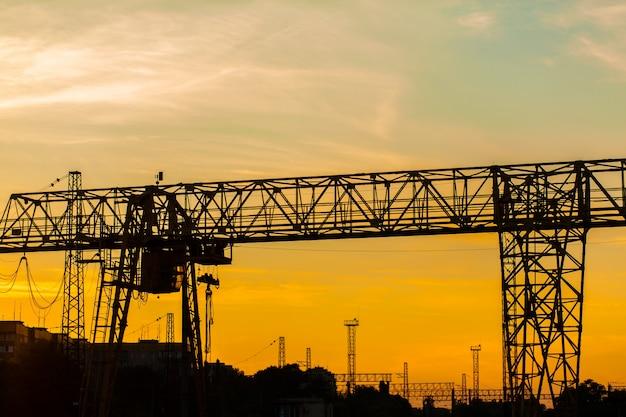 Ponte rolante na estação ferroviária. silhueta de guindaste no fundo por do sol. conceito de indústria pesada.