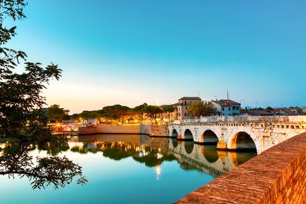Ponte romana histórica de tiberius sobre o rio marecchia durante o por do sol em rimini, itália.