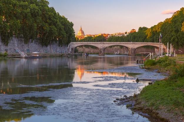 Ponte saint angel e a catedral de saint peter com um reflexo de espelho no rio tibre na manhã ensolarada em roma, itália.