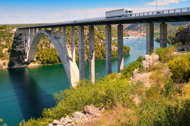 Ponte sibenik através do desfiladeiro do rio krka, vista para a cidade de scradin. litoral romântico no norte da dalmácia, croácia.