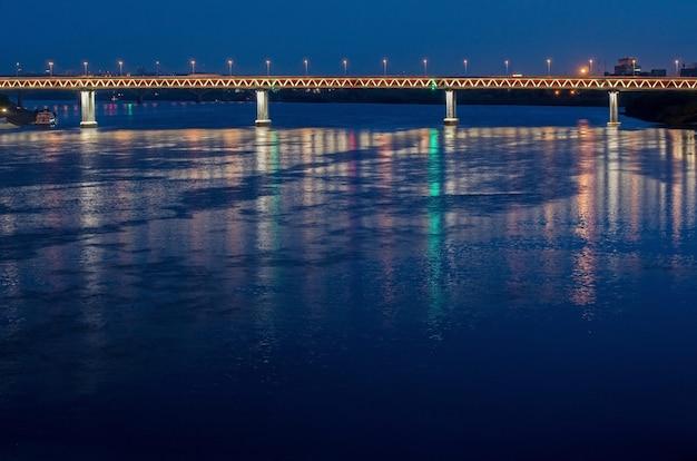 Ponte sobre o rio à noite. trânsito rápido e ponte de carros para fluxo de tráfego. paisagem de belas luzes à noite.