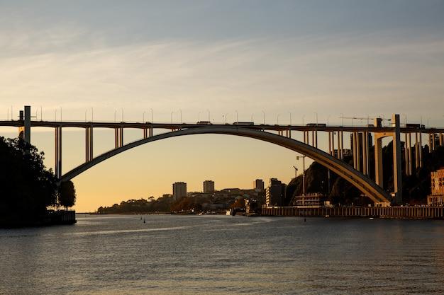 Ponte sobre o rio ao pôr do sol. porto, portugal