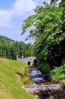 Ponte sobre um riacho de rio de fluxo rápido ponte de madeira de verão