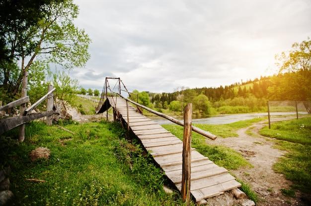 Ponte suspensa de madeira da montanha do rio dos cárpatos