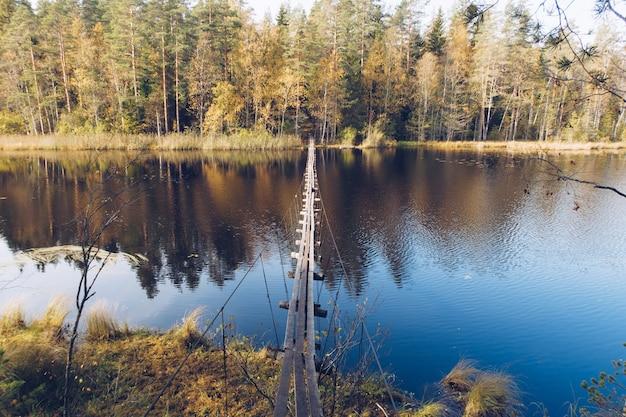 Ponte suspensa de madeira longa estreita sobre o lago na carélia, na rússia. bela paisagem de outono com fotografia de rio e floresta