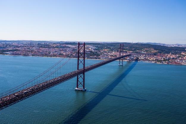 Ponte suspensa sobre o tejo cristo revere, em lisboa, portugal, vista da estátua de cristo-rei