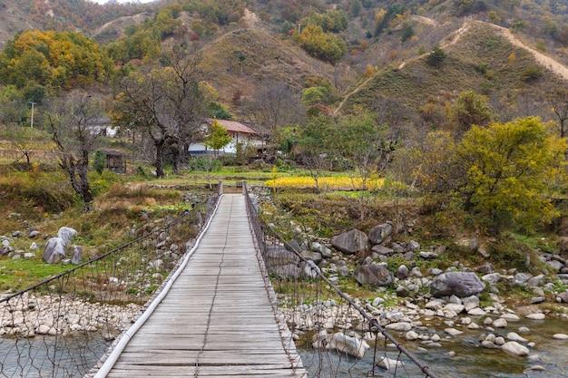 Ponte suspensa sobre um rio em um desfiladeiro de montanha. ponte de madeira até a casa. província de shaanxi