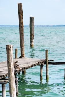 Ponte velha com barras com gaivotas na paisagem do lago de garda