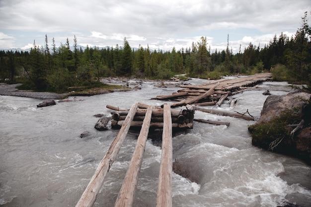 Ponte velha, quebrada, de madeira sobre o rio nas montanhas de altai.