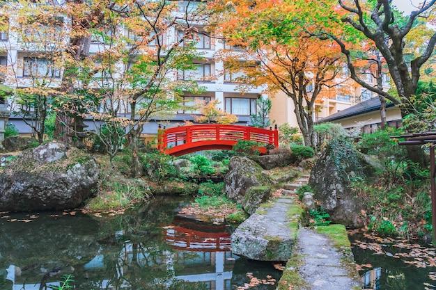 Ponte vermelha no parque verde japonês com folhas coloridas de outono, outono japonês