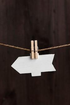 Ponteiro de seta em branco com prendedores de roupa na corda, fundo de madeira. placa de identificação pequena. copie o espaço. quadro vertical.
