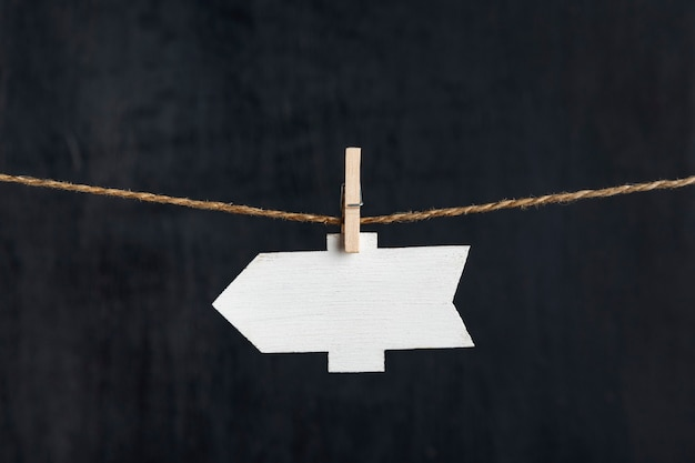 Ponteiro de seta em branco pendurar com prendedores de roupa na corda em fundo preto. copie o espaço. lugar para o seu texto.