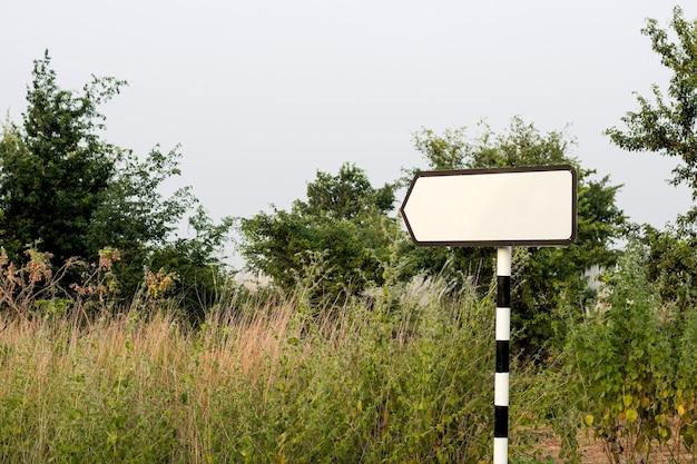 Ponteiro de trilha em branco ou sinal de seta direcional dentro da selva