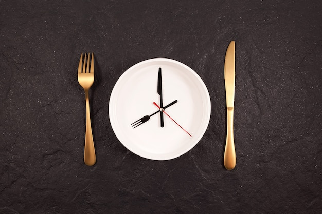 Ponteiros do relógio em um prato branco. garfo e faca de ouro em uma mesa de pedra escura