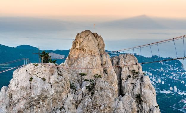 Pontes de corda e uma cruz no pico ai petri nas montanhas da crimeia