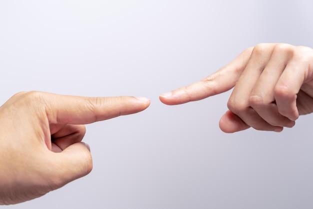 Ponto de dedo tocando as mãos de homens e mulheres, quase tocando.