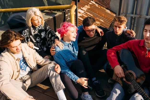 Ponto de encontro de grupo de amigos. cantando para um violão. estilo de vida dos espíritos livres. lazer de adolescentes hipster urbano