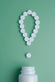 Ponto de exclamação com pílulas derramou de um frasco de medicamento. vista do topo. lay plana.