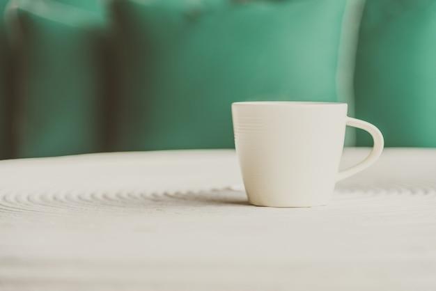 Ponto de foco seletivo no café preto em copo branco - efeito de filtro vintage