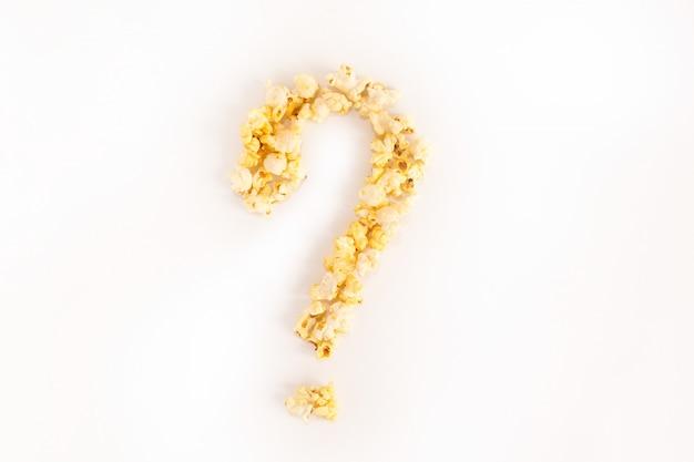 Ponto de interrogação alinhado com grãos de milho em um fundo branco.