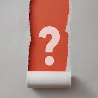 Ponto de interrogação branco em negrito emoldurado por papel cinza rasgado enrolado cuidadosamente na parte inferior, revelando um fundo vermelho em formato quadrado