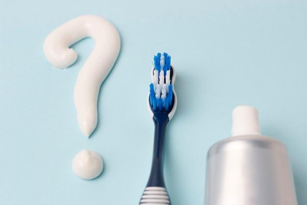 Ponto de interrogação de pasta de dentes e escova de dentes no fundo azul, conceito de escolha
