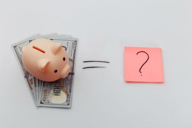 Ponto de interrogação e notas de dólar com cofrinho.