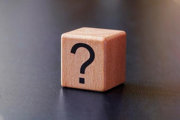 Ponto de interrogação em um pequeno bloco de madeira