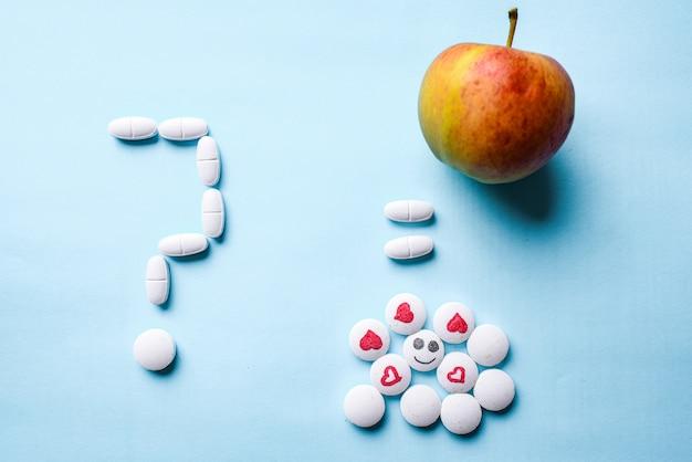 Ponto de interrogação feito de pílulas brancas, uma maçã madura e um monte de pílulas brancas com um rosto e um coração