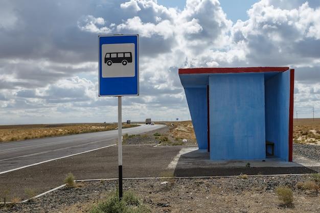 Ponto de ônibus azul e uma placa de ponto de ônibus em um pilar na estepe do cazaquistão