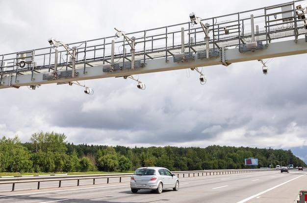 Ponto de pedágio da estrada contra o céu nublado com carro na estrada