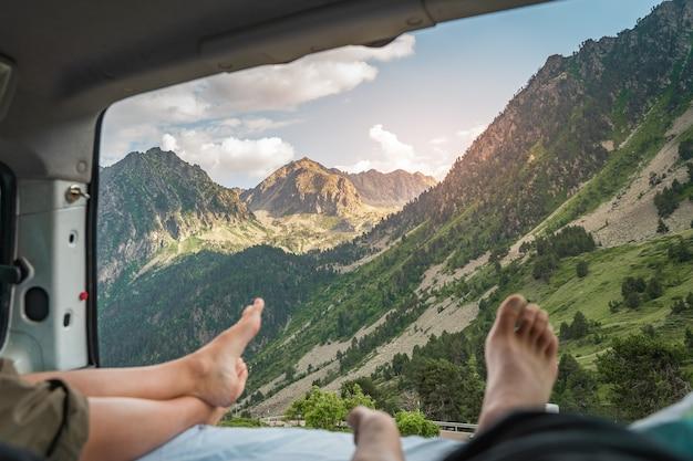 Ponto de vista das pernas de um casal romântico dentro de uma velha van apreciando a incrível paisagem juntos