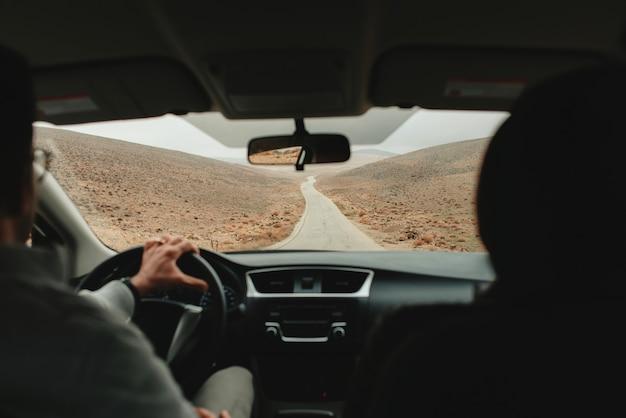 Ponto de vista de dentro do carro, olhando uma estrada deserta.
