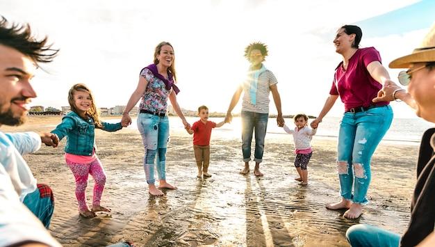 Ponto de vista de famílias jovens dançando na praia no anel ao redor do estilo rosado