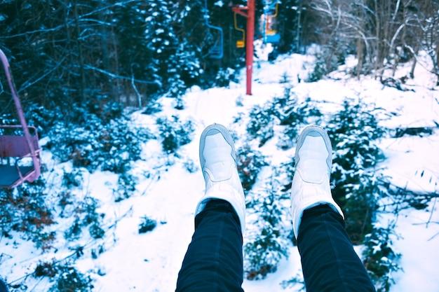 Ponto de vista de mulheres com pernas de jeans pretas e sapatos brancos na cadeira de um pequeno teleférico grunge movendo-se pela floresta de inverno coberta de neve