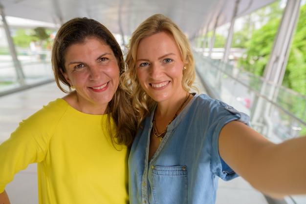 Ponto de vista pessoal de duas mulher feliz tomando selfie
