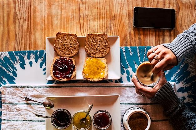 Ponto de vista superior vertical de mulher tomando café da manhã no hotel ou em casa