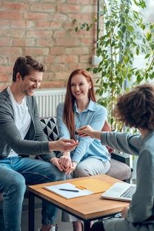 Ponto importante. corretor dando chave imobiliária para comprador sorridente e ao lado da jovem esposa feliz sentada em um escritório moderno durante o dia