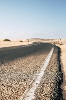 Ponto térreo com vista de uma longa estrada de asfalto na natureza ao ar livre do deserto