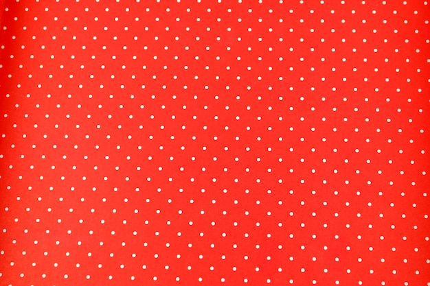 Pontos brancos sobre fundo e textura de tecido vermelho de bolinhas