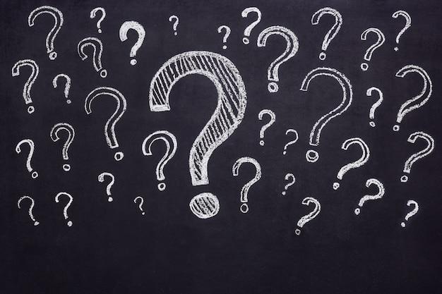 Pontos de interrogação desenhados a giz em um quadro negro