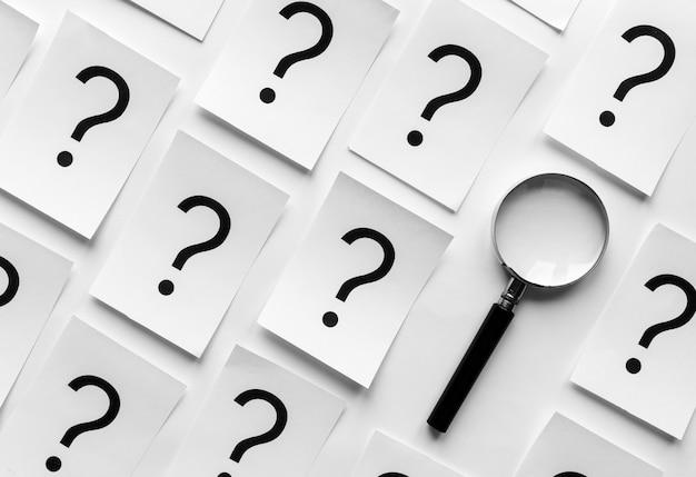 Pontos de interrogação e lupa orientados diagonalmente