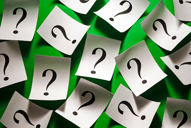 Pontos de interrogação espalhados aleatoriamente em papel branco