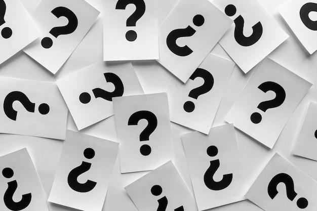 Pontos de interrogação negros em negrito em cartões de papel