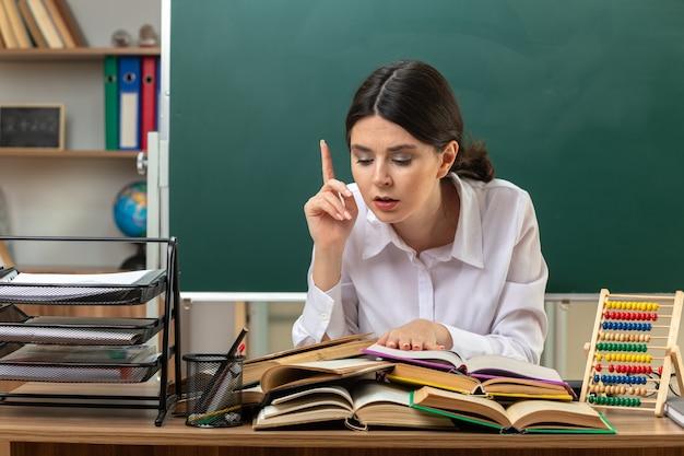 Pontos impressionados para a jovem professora lendo livro na mesa sentada à mesa com ferramentas da escola na sala de aula