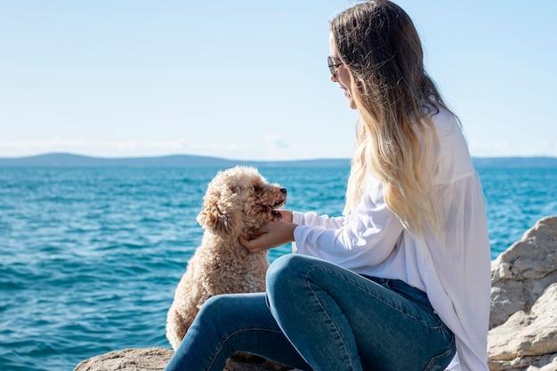 Poodle de alto ângulo com proprietário na beira-mar