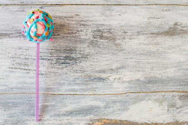 Pop para bolo de cor viva. glacê e flores pequenas. lanche doce para festa infantil. design de confeitaria.