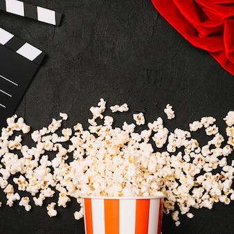 Popcorn derramou perto de clapperboard e pano vermelho
